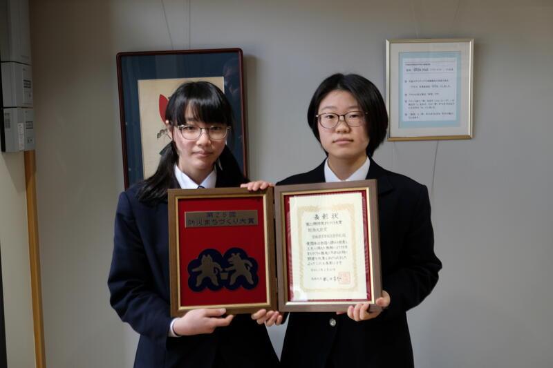 賞状と盾を持つ生徒会長の櫻井乃綾さん(左)と副会長の金谷紅さん(右)